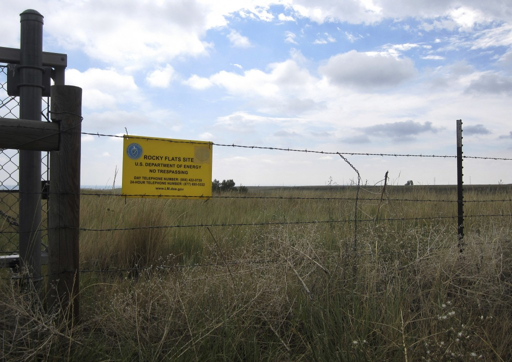 """FILE - This Aug. 11, 2017, file photo shows a """"No Trespassing"""" sign hanging on a fence surrounding part of the former Rocky Flats nuclear weapons plan"""