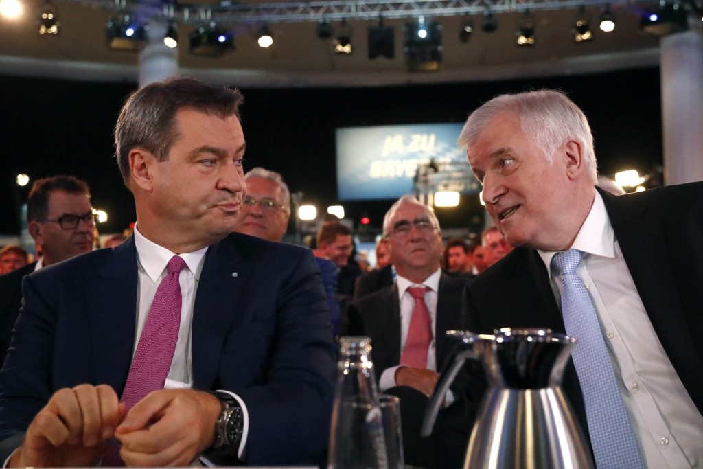 Bavarian State Governor Markus Soeder, left, talks to German Interior Minister Horst Seehofer, right, prior to a party convention of the German Christ