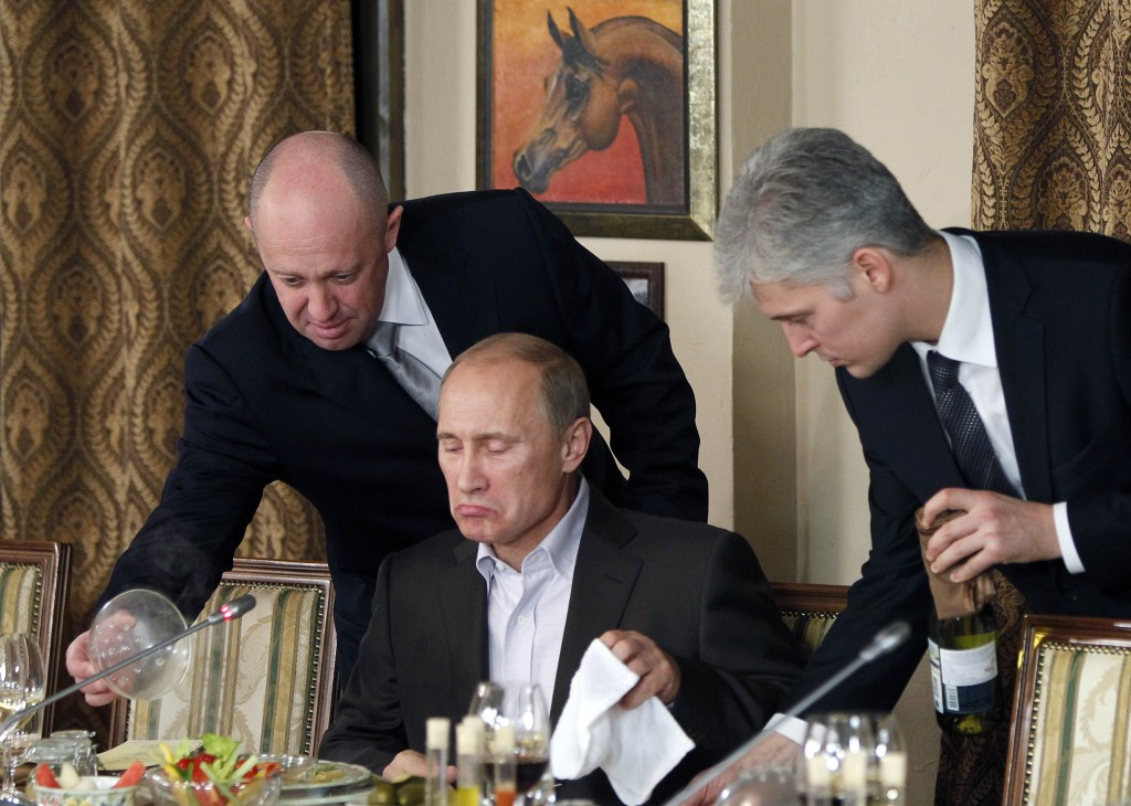 FILE - In this Friday, Nov. 11, 2011 file photo, businessman Yevgeny Prigozhin, left, serves food to Russian Prime Minister Vladimir Putin, center, du