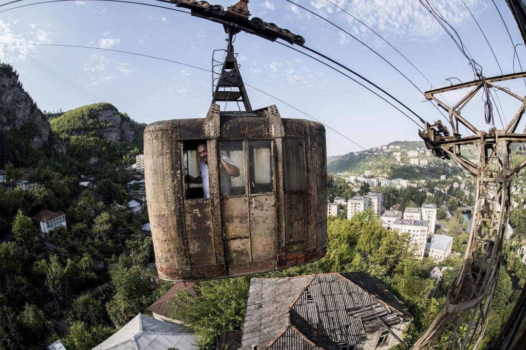 In this photo taken on Friday, Aug. 31, 2018, a local man looks through a window of a rusted cable car riding over the Georgian city of Chiatura, abou