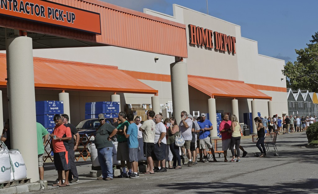 FILE - In this Wednesday, Sept. 12, 2018 file photo, people line up outside a Home Depot for a new supply of generators and plywood in advance of Hurr