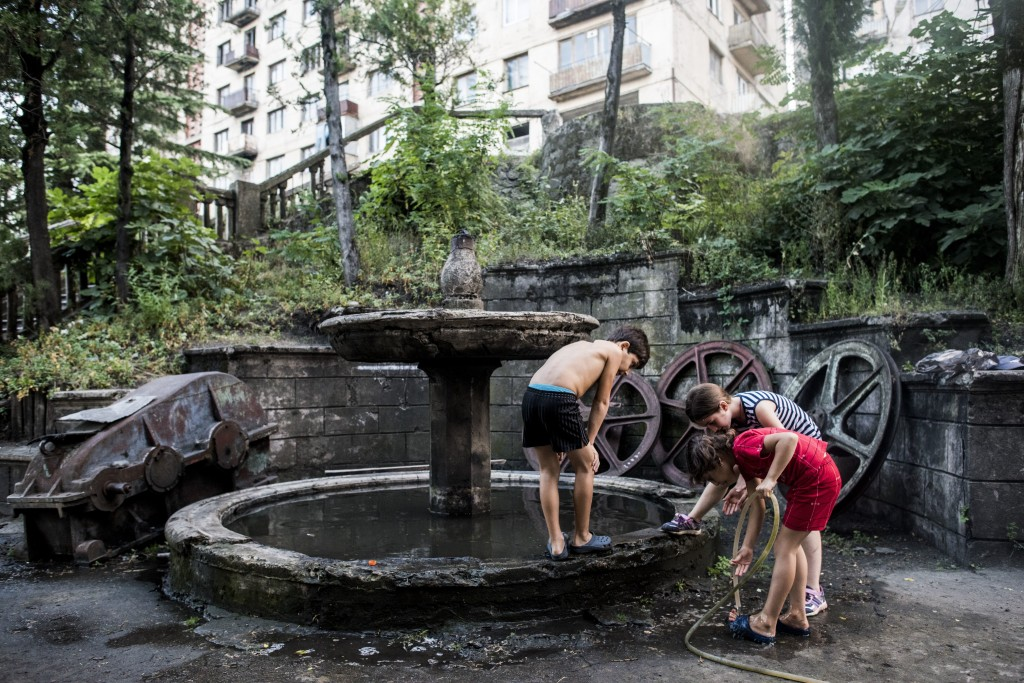 In this photo taken on Thursday, Aug. 30, 2018, children play at a broken fountain with rusted parts of a cable car's system next to a cable car stati