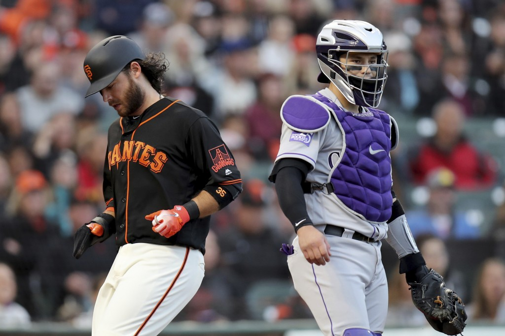 San Francisco Giants shortstop Brandon Crawford (35) scores in front of Colorado Rockies catcher Tony Wolters (14) during a baseball game in San Franc