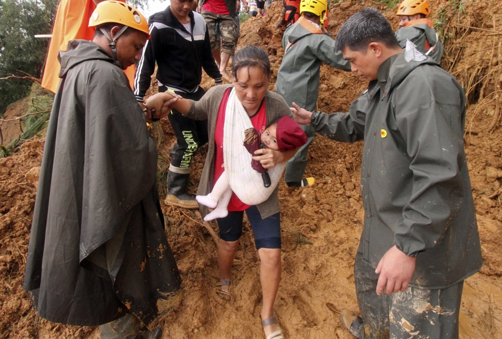 Rescuers assist a mother and her child as they evacuate to safer grounds following landslides that hit Itogon township, Benguet province in the northe