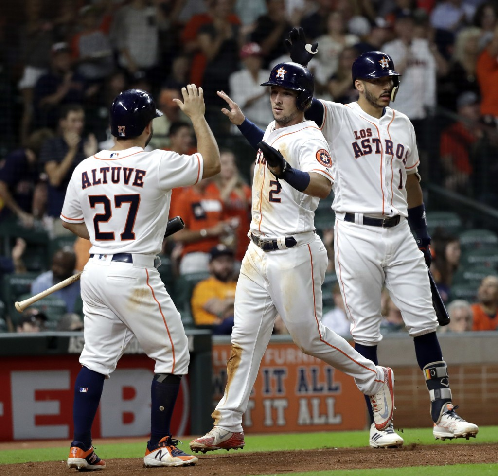 Houston Astros' Alex Bregman (2) and Jose Altuve (27) celebrate after scoring as Carlos Correa (1) waits to bat against the Arizona Diamondbacks durin