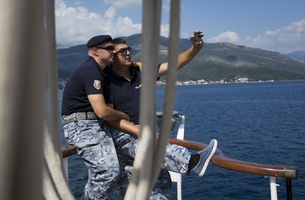 In this Sept. 6, 2018 photo, sailors take selfie photos aboard the training ship 'Jadran' as they sail near the port of Tivat, Montenegro. Montenegro