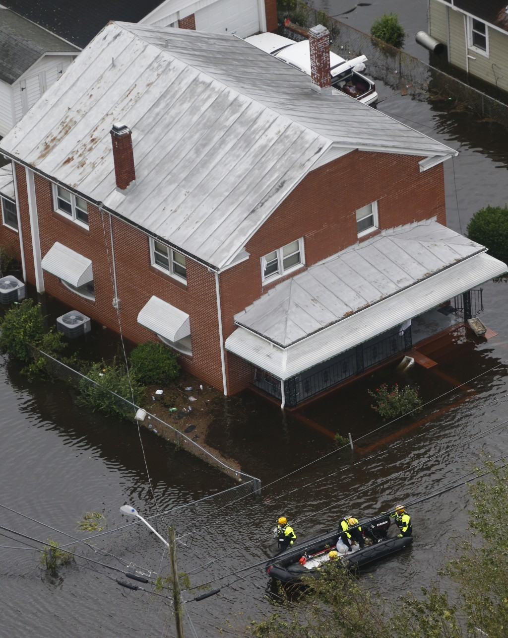 Rescue personnel use a small boat as they go house to house checking for flood victims from tropical storm Florence in New Bern, NC., Saturday, Sept.