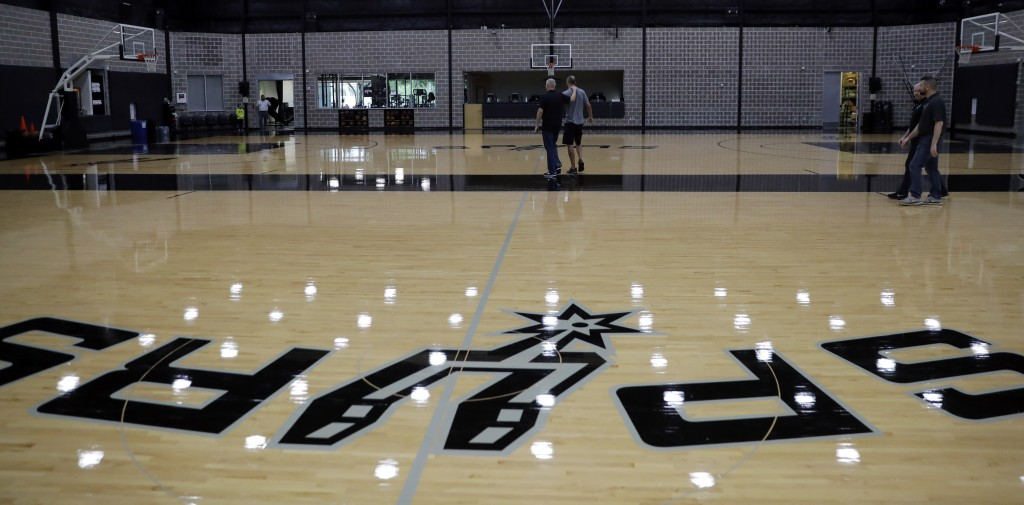 Former San Antonio Spurs guard Manu Ginobili, center right, walks with Spurs director of communications Tom James, center left, after talking to the m