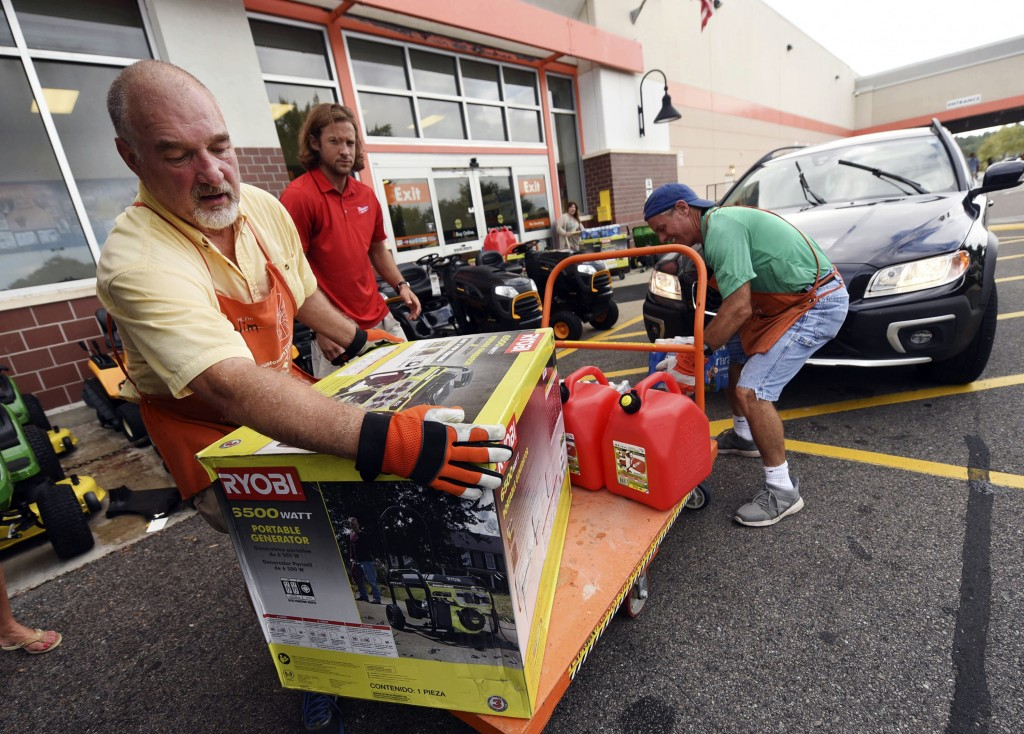 FILE - In this Monday, Sept. 10, 2018 file photo, Jim Craig, David Burke and Chris Rayner load generators as people buy supplies at The Home Depot in