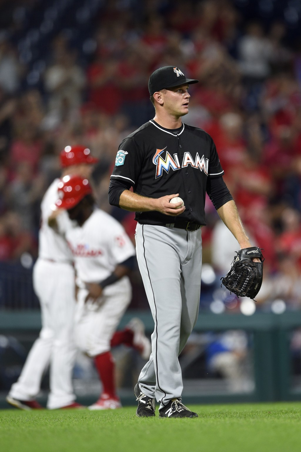 Miami Marlins' Drew Rucinski walks back to the mound after giving up a three-run home run to Philadelphia Phillies' Cesar Hernandez during the fifth i
