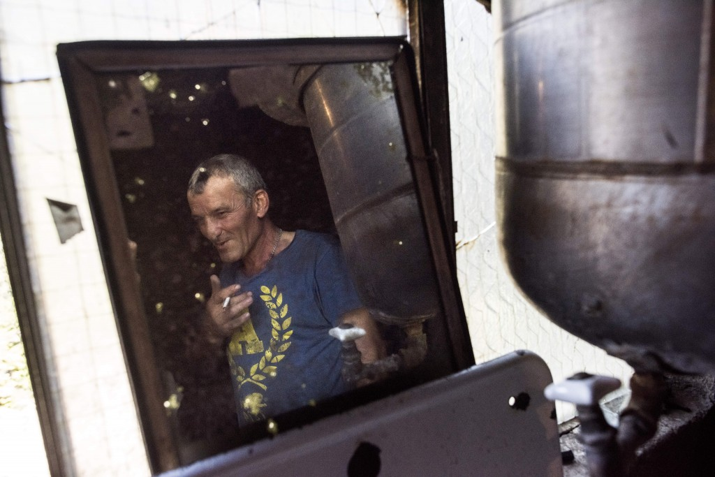In this photo taken on Wednesday, Aug. 29, 2018, Anzor, a manganese plant worker who uses a cable car to get to his place of work, is reflected in a m...