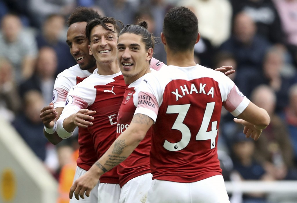 Arsenal's Mesut Ozil, centre, celebrates scoring his side's second goal of the game with teammates, during the English Premier League soccer match bet...