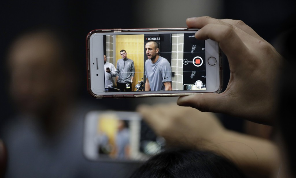 Former San Antonio Spurs guard Manu Ginobili is recorded on a mobile phone as he talks to the media at the NBA basketball team's practice facility, Sa