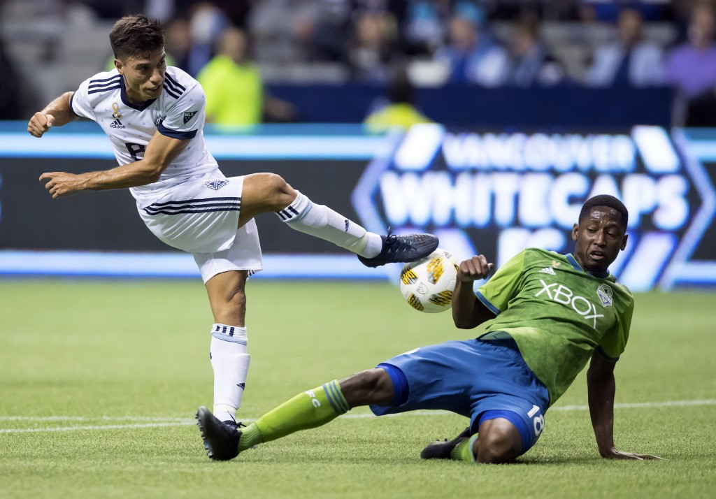 Vancouver Whitecaps' Nicolas Mezquida, left, has his shot blocked by Seattle Sounders' Kelvin Leerdam during the first half of an MLS soccer match, Sa...