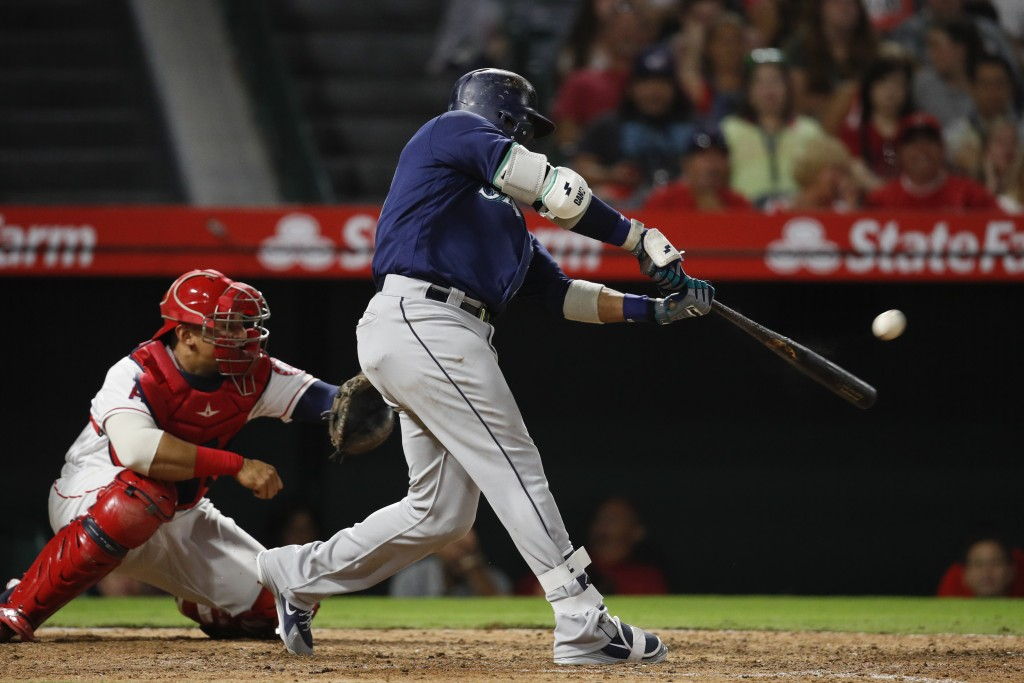 Seattle Mariners' Robinson Cano connects for a three-run double during the eighth inning of a baseball game against the Los Angeles Angels, Saturday,