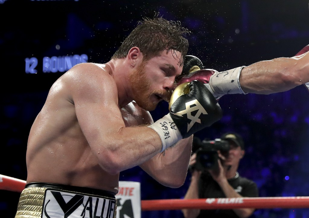 Canelo Alvarez takes a punch from Gennady Golovkin in the 10th round during a middleweight title boxing match, Saturday, Sept. 15, 2018, in Las Vegas....