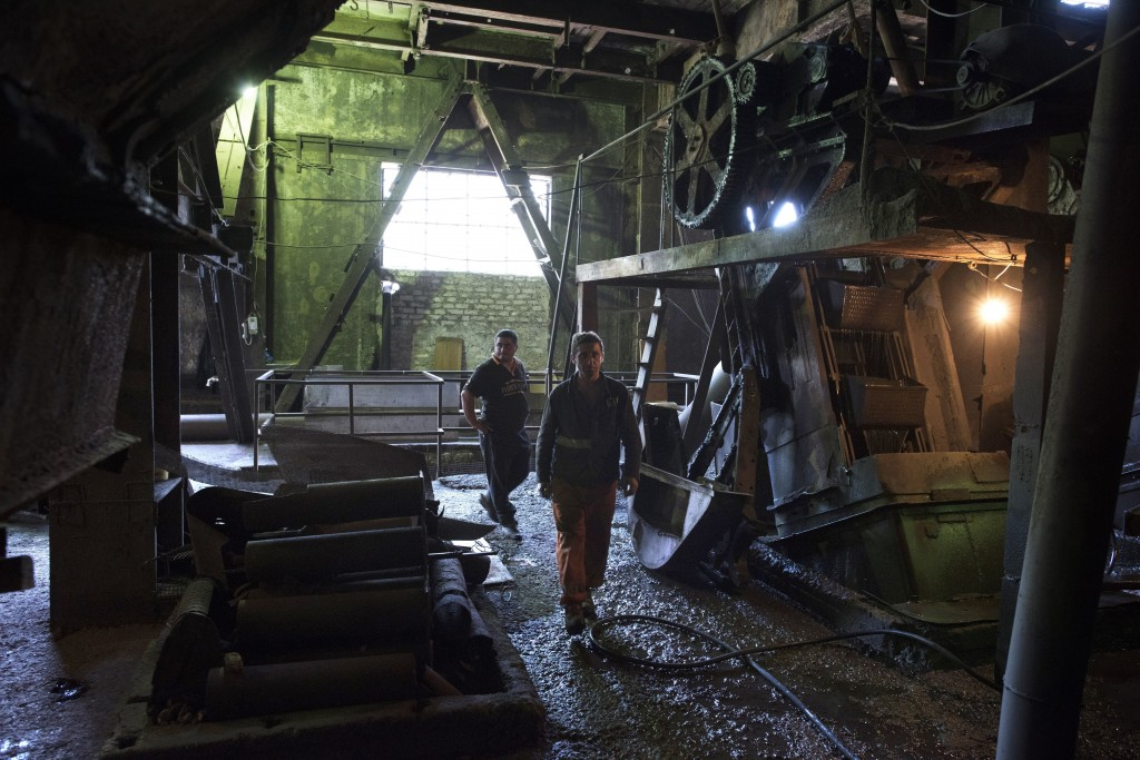 In this photo taken on Wednesday, Aug. 29, 2018, two Georgian miners walk inside the very old manganese plant after riding a cable car, in the Georgia...