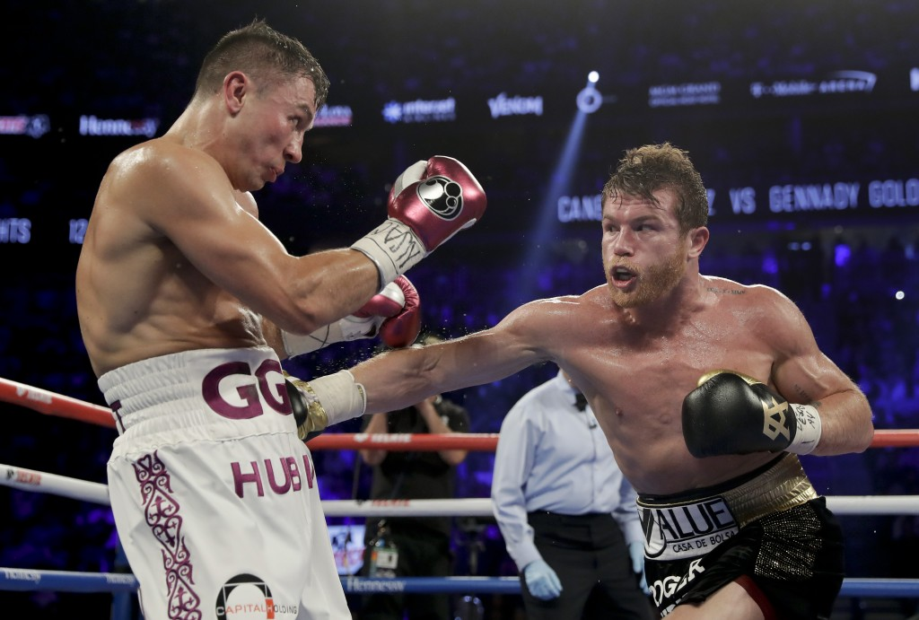 Canelo Alvarez, right, and Gennady Golovkin trade punches in the fourth round during a middleweight title boxing match, Saturday, Sept. 15, 2018, in L...