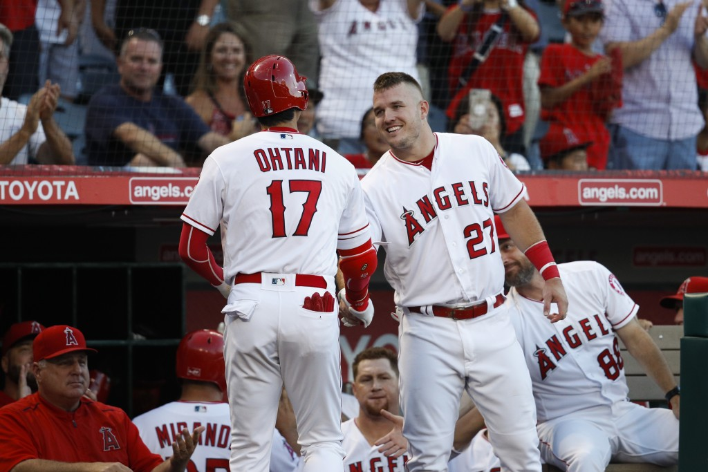 Los Angeles Angels' Shohei Ohtani shakes hands with Mike Trout after hitting a home run during the first inning of a baseball game against the Seattle