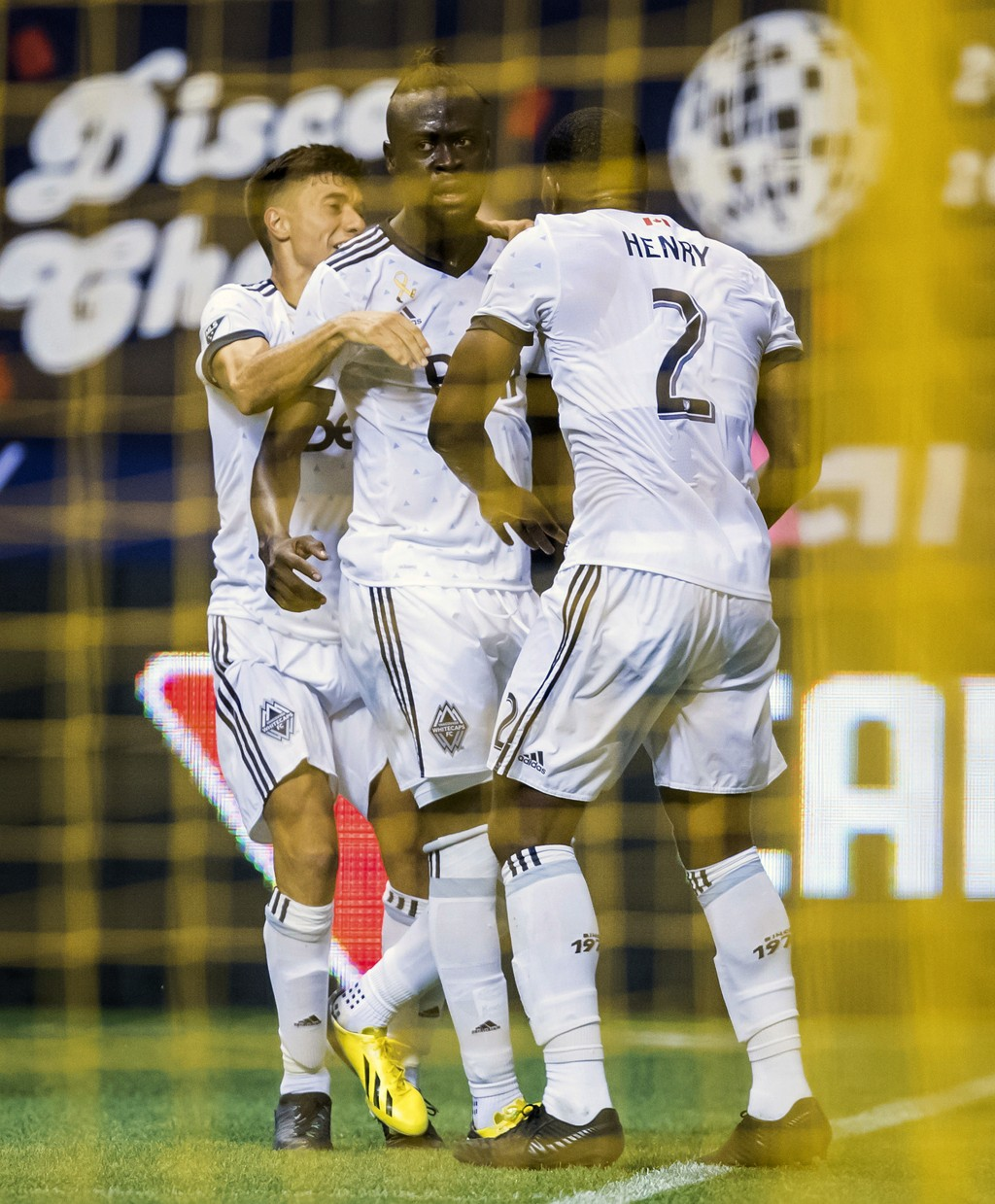 Vancouver Whitecaps' Nicolas Mezquida, from left to right, Kei Kamara and Doneil Henry celebrate Kamara's goal against the Seattle Sounders during the...