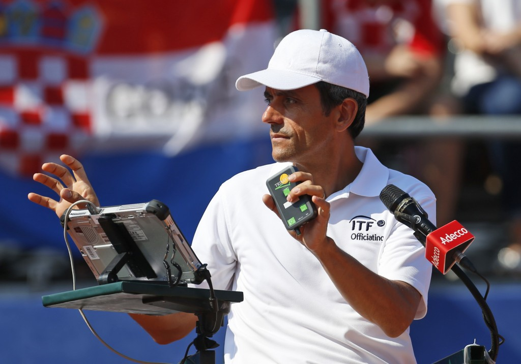 Tennis umpire Carlos Ramos, left, prepares to officiate the Davis Cup semifinal singles match between Sam Querrey of the United States and  Marin Cili