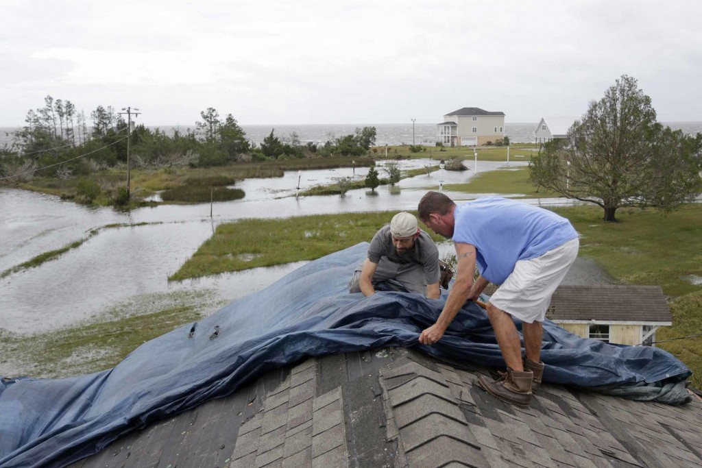 Jeff Pyron, left, and Daniel Lilly cover Lilly's roof after Hurricane Florence hit Davis N.C., Saturday, Sept. 15, 2018. The town had 4 1/2 feet of st