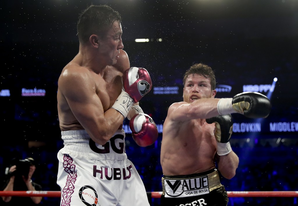 Gennady Golovkin, left, and Canelo Alvarez trade punches in the fifth round during a middleweight title boxing match, Saturday, Sept. 15, 2018, in Las