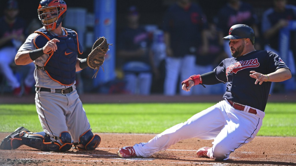 Cleveland Indians' Yonder Alonso slides safely into home plate as Detroit Tigers catcher James McCann looks for the ball in the first inning of a base