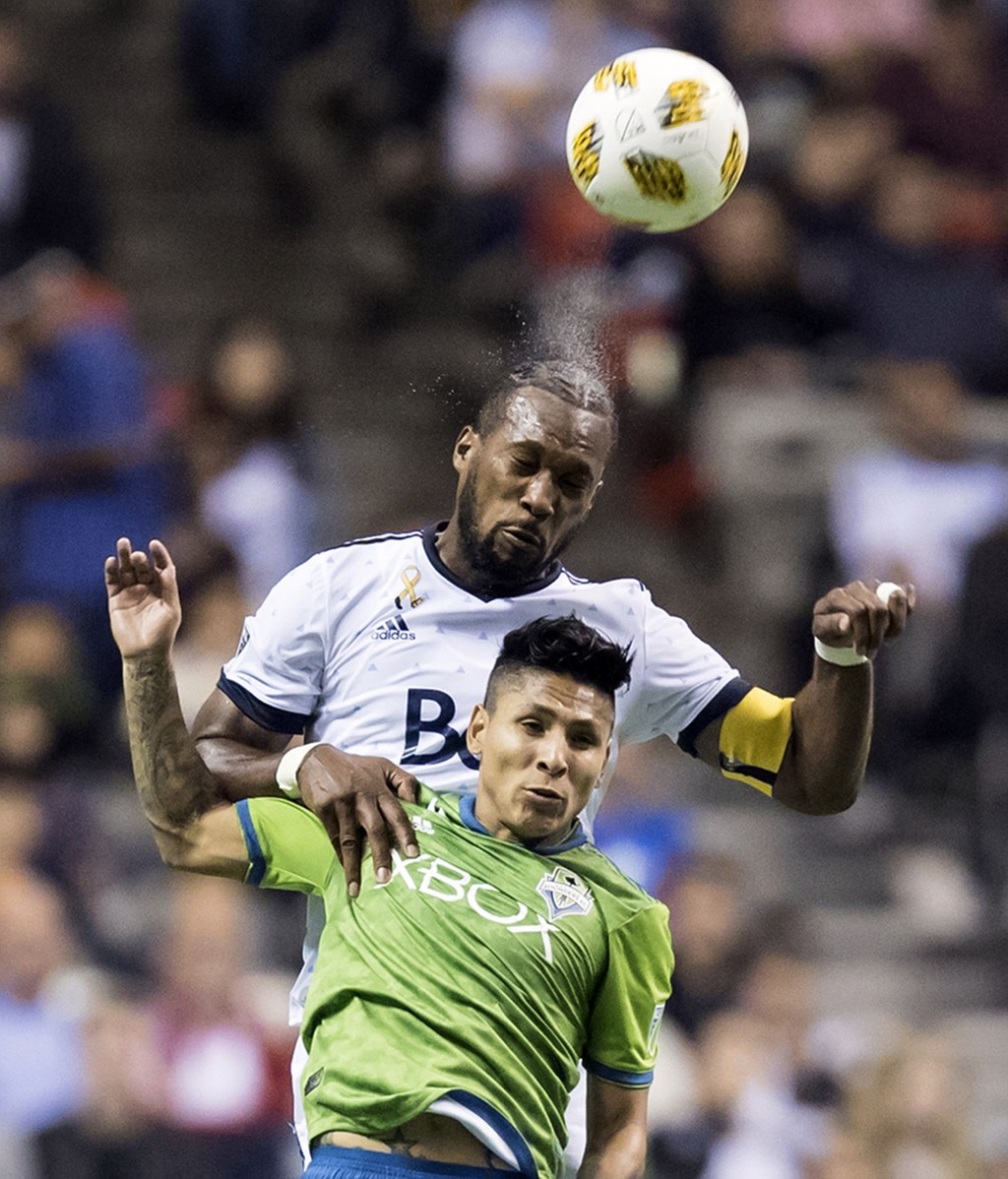 Vancouver Whitecaps' Kendall Waston, back, heads the ball behind Seattle Sounders' Raul Ruidiaz during the first half of an MLS soccer match, Saturday...