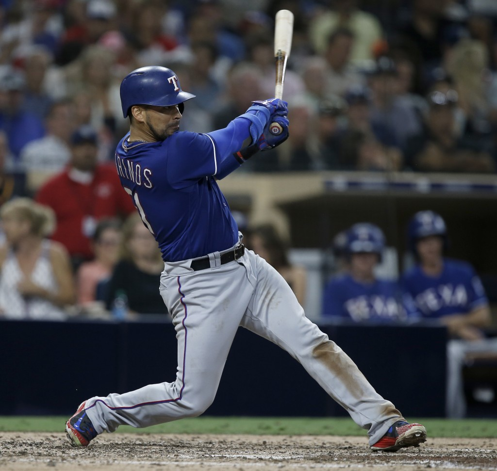 Texas Rangers' Robinson Chirinos hits a three-run double against the San Diego Padres during the sixth inning of a baseball game in San Diego, Saturda