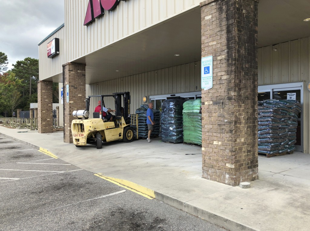 In this Wednesday, Sept. 12, 2018 photo, Manager Tom Roberts watches as an employee positions a pallet of mulch to protect the Ace Hardware store from