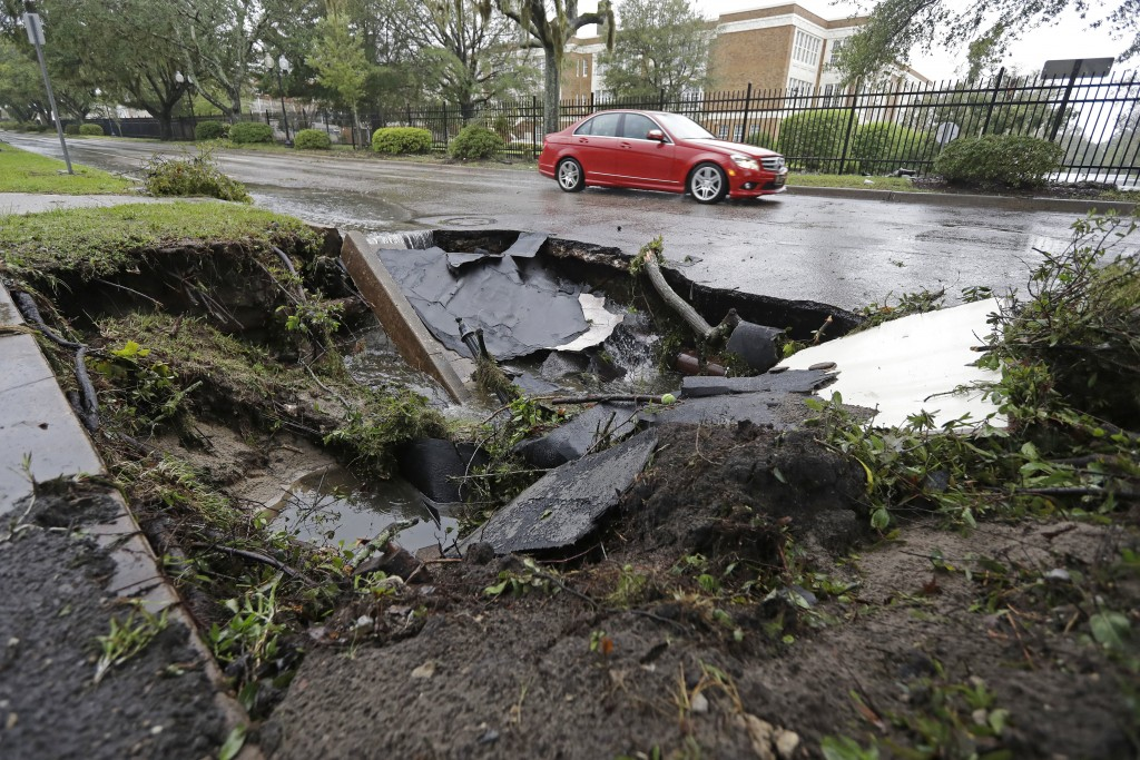 A car travels past a sinkhole in downtown Wilmington, N.C., after Hurricane Florence traveled through the area Sunday, Sept. 16, 2018. (AP Photo/Chuck