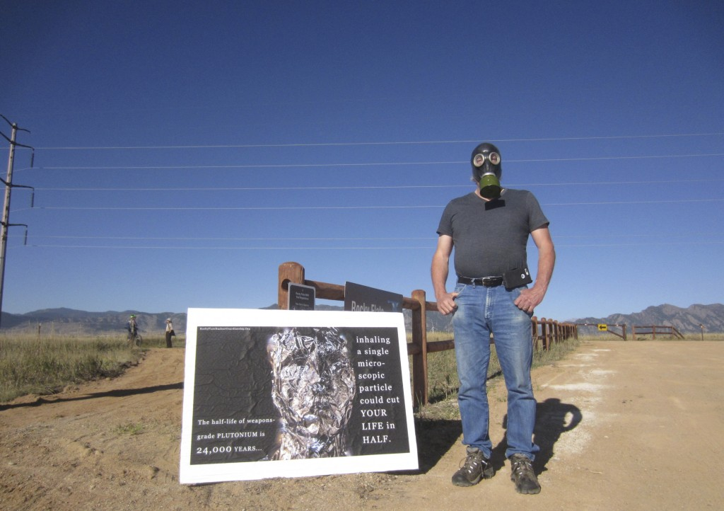 Stephen Parlato wears a gas mask next to his sign warning about the dangers of plutonium at Rocky Flats National Wildlife Refuge outside Denver on Sat