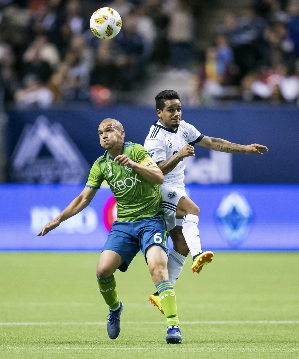 Seattle Sounders' Osvaldo Alonso, left, and Vancouver Whitecaps' Cristian Techera collide during the first half of an MLS soccer match, Saturday, Sept