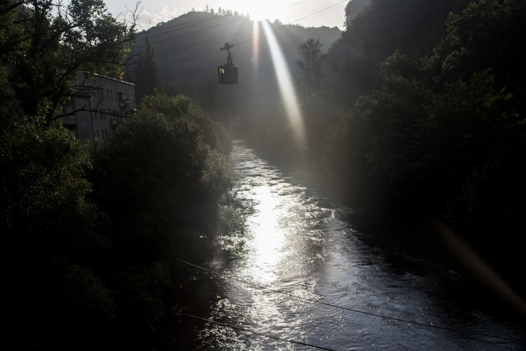 In this photo taken on Friday, Aug. 31, 2018, a cable car moves between two mountains during a sun rise in the Georgian city of Chiatura, about 200 ki...