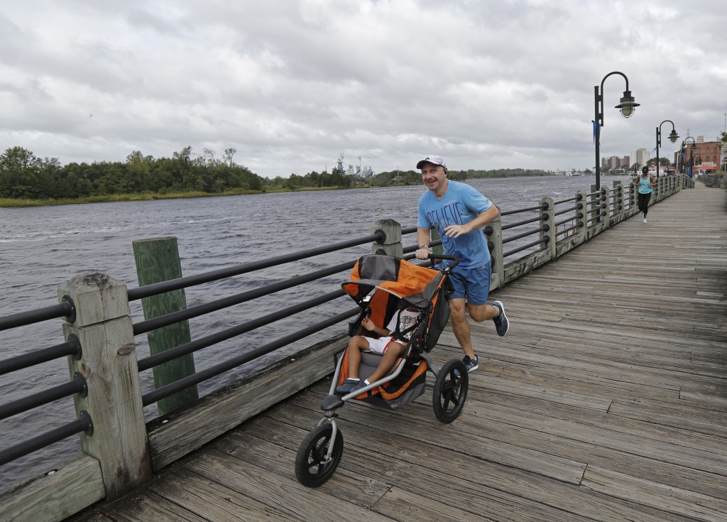 FILE - In this Thursday, Sept. 13, 2018 file photo, a man jogs down the boardwalk by the Cape Fear River in downtown Wilmington, N.C., as Hurricane Fl
