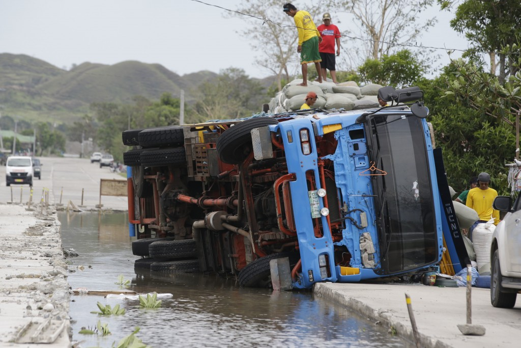 Workers transfer sacks of grains from a toppled truck that fell into an area where the road was being repaired following floodwaters in Cagayan provin