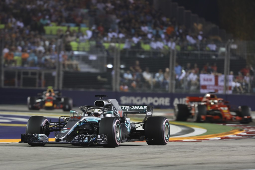 Mercedes driver Lewis Hamilton of Britain, left, steers his car ahead of Ferrari driver Sebastian Vettel of Germany during the Singapore Formula One G