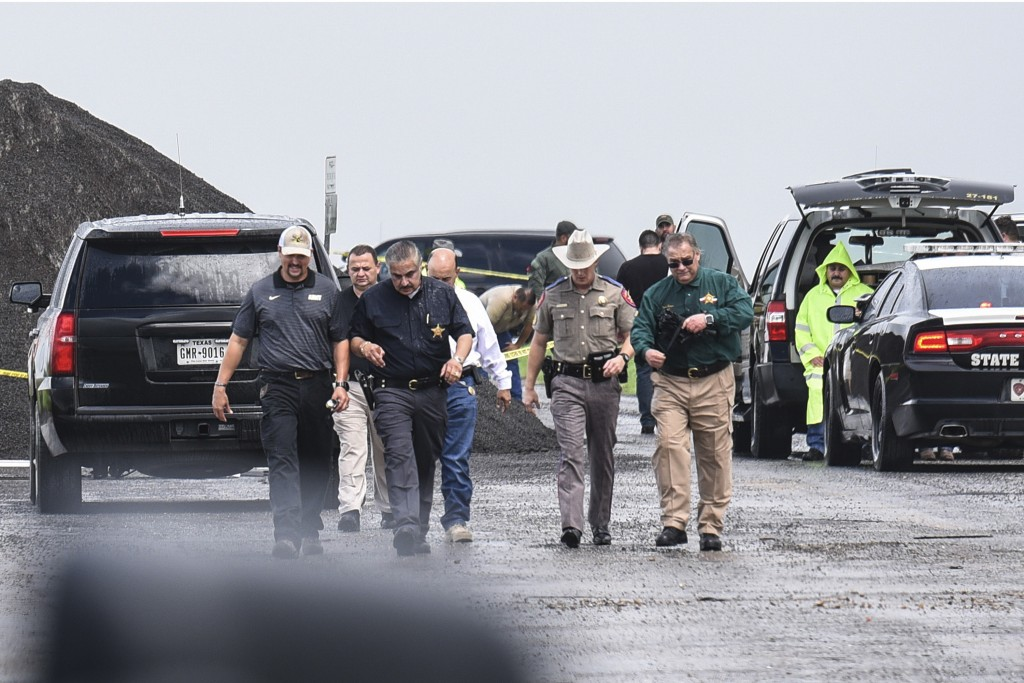 Law enforcement officers gather near the scene where the body of a woman was found near Interstate 35 north of Laredo, Texas on Saturday, Sept. 15, 20