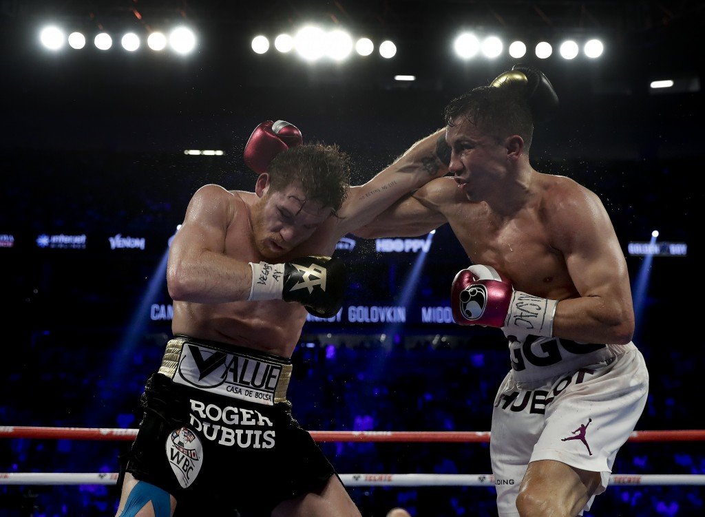 Canelo Alvarez, left, and Gennady Golovkin trade punches in the fourth round during a middleweight title boxing match, Saturday, Sept. 15, 2018, in La