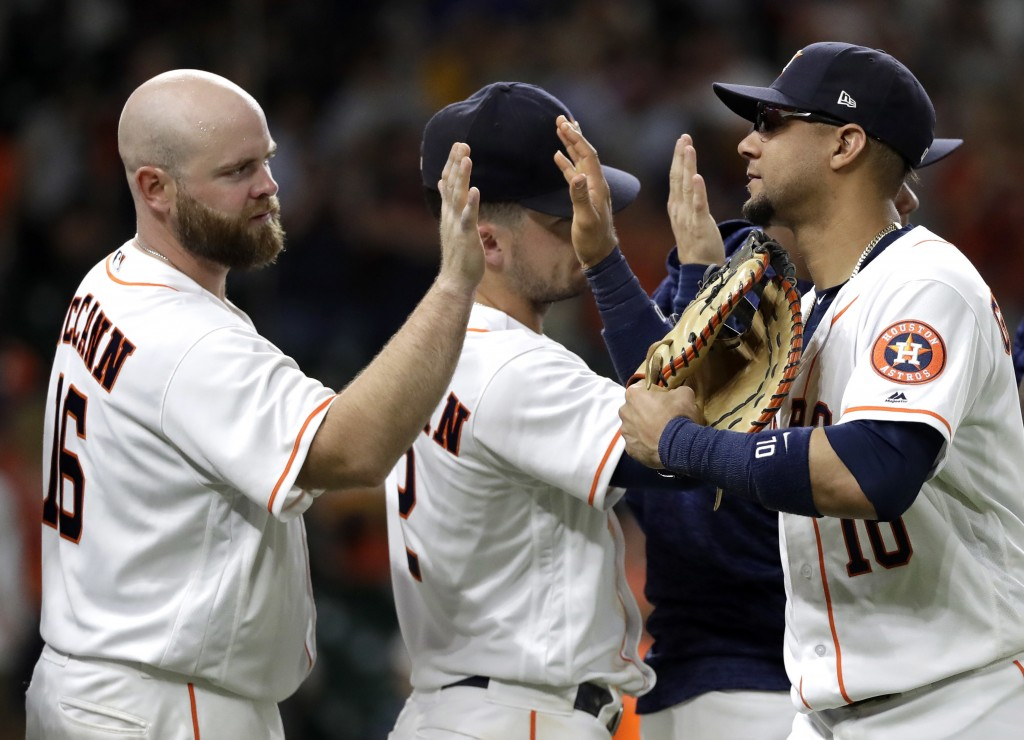 Houston Astros' Yuli Gurriel (10) celebrates with Brian McCann (16) and Alex Bregman (2) after a baseball game against the Arizona Diamondbacks Saturd