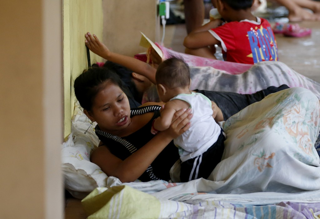 FILE - In this Saturday, Sept. 15, 2018, file photo, a mother cuddles her child as they seek temporary shelter along a corridor of an evacuation cente