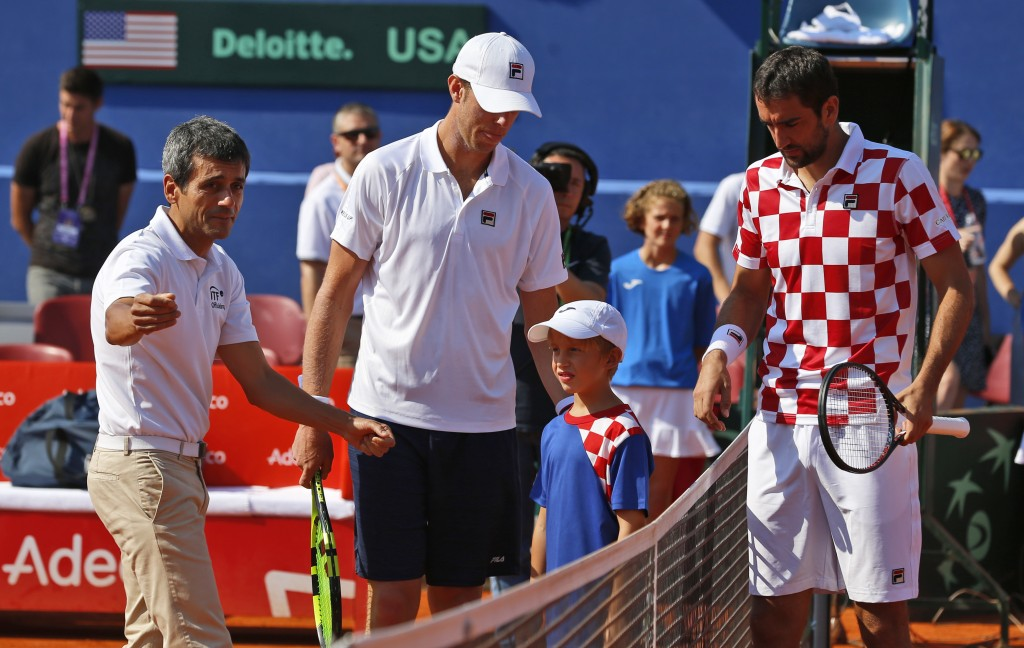 Tennis umpire Carlos Ramos, left, prepares to officiate the Davis Cup semifinal singles match between  Sam Querrey, center of the United States and  M