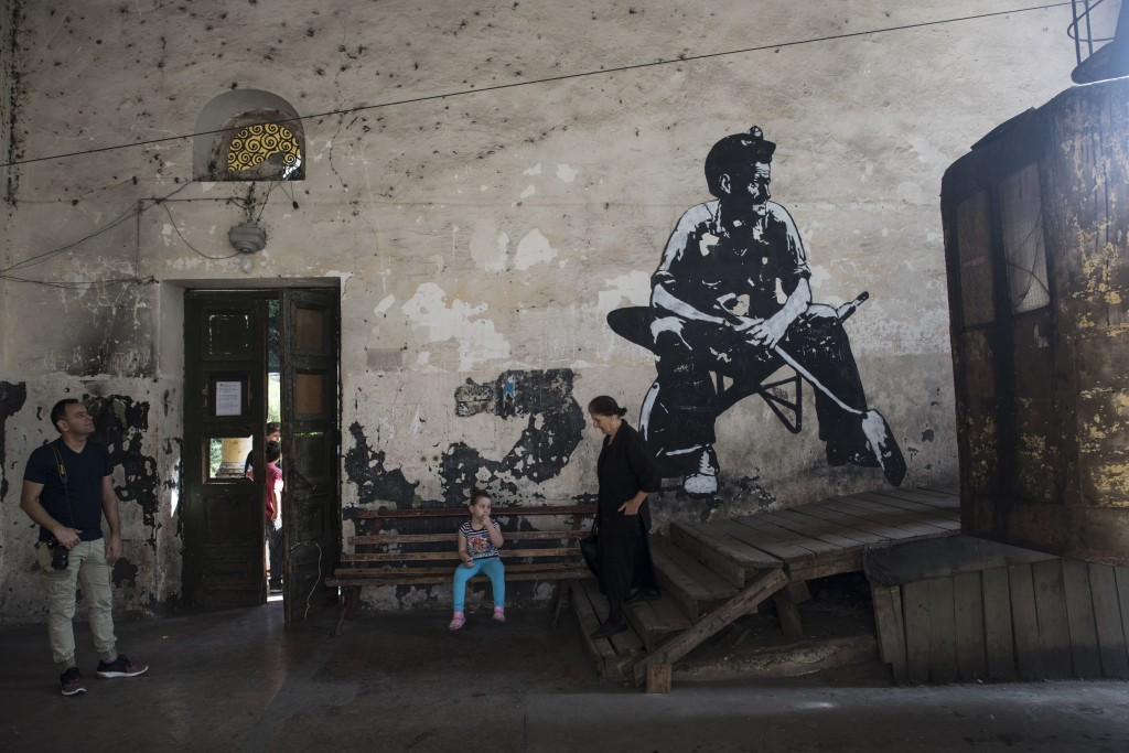 In this photo taken on Friday, Aug. 31, 2018, local people and a tourist wait at a a cable car station decorated with a graffiti of a Georgian miner i...