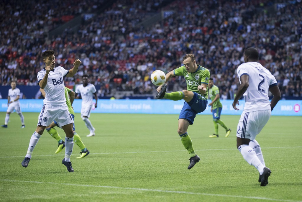 Seattle Sounders' Brad Smith, second from right, kicks the ball away from Vancouver Whitecaps' Nicolas Mezquida, left, and Doneil Henry, right, during
