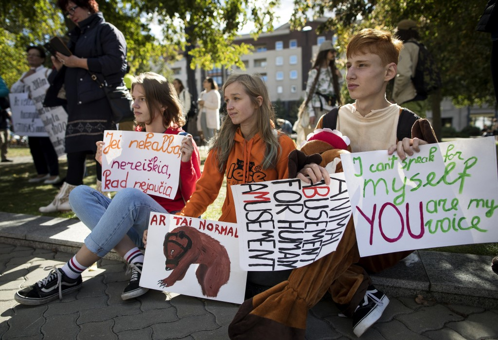 Animal rights activists attend a mass protest rally near Lithuania parliament in Vilnius, Lithuania, Sunday, Sept. 16, 2018. Animal rights activists s