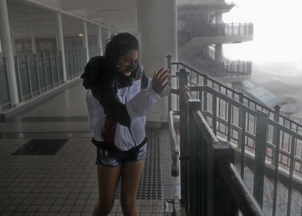 A girl stands against strong wind caused by Typhoon Mangkhut at a pier on the waterfront of Victoria Habour Hong Kong, Sunday, Sept. 16, 2018. Hong Ko