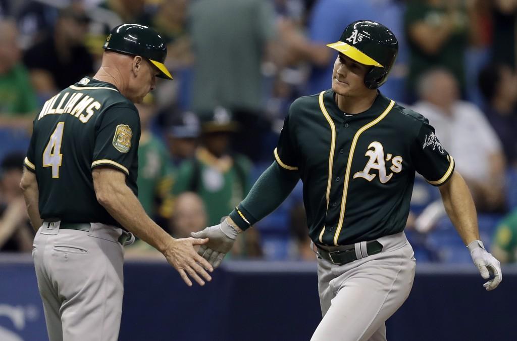 Oakland Athletics' Matt Chapman, right, shakes hands with third base coach Matt Williams after Chapman hit a home run off Tampa Bay Rays pitcher Sergi