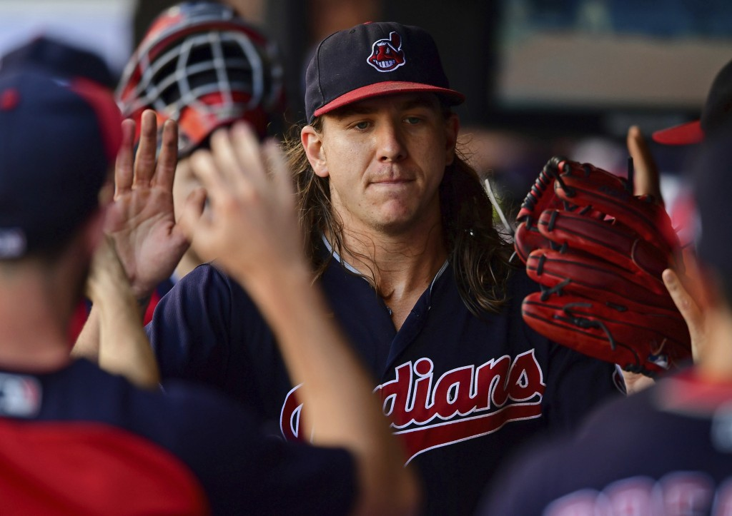 Cleveland Indians starting pitcher Mike Clevinger is congratulated int he dugout in the fifth inning of a baseball game against the Detroit Tigers, Sa