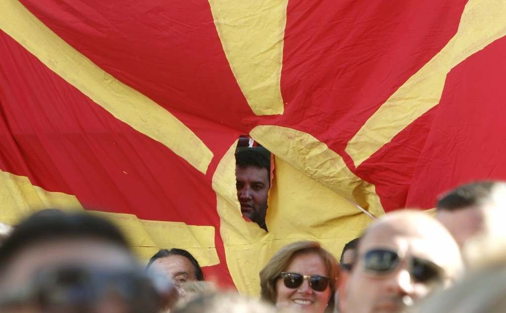 "A man peeps out through a torn Macedonian flag during a pre-referendum rally named ""For European Macedonia"", in Skopje, Macedonia, Sunday, Sept. 16, 2"